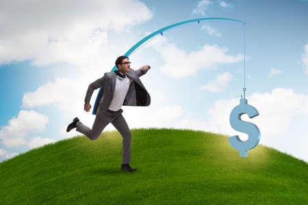 Businessman chasing money on fishing rod Stock Photo