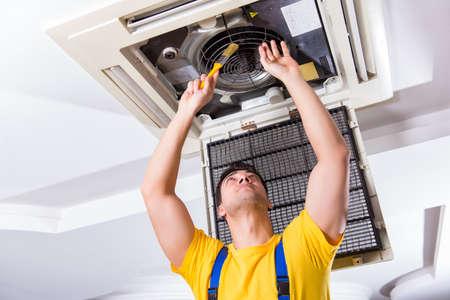 Repairman repairing ceiling air conditioning unit Stockfoto