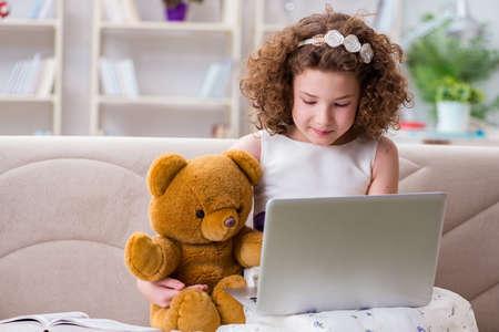 Little girl surfing internet on laptop