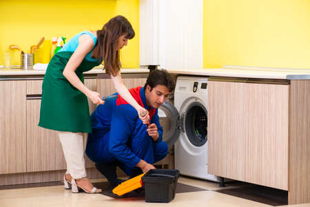 Contractor repairing washing machine at home