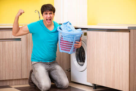 A young husband doing laundry at home Standard-Bild