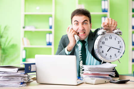 Businessman angry with excessive work sitting in the office in t Foto de archivo