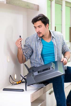 Young man husband repairing tv at home Stock Photo