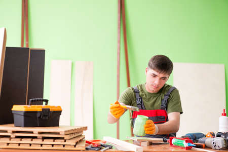 Young man carpenter working in workshop 스톡 콘텐츠
