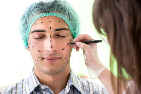 Plastic surgeon preparing for operation on man face