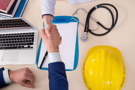 Doctor and manager agreeing industrial insurance coverage Stock Photo