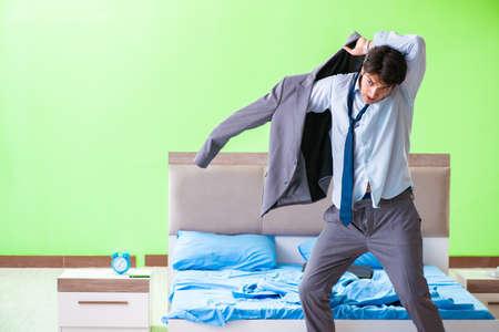 Empleado en el dormitorio llegando tarde a su trabajo en la gestión del tiempo Foto de archivo