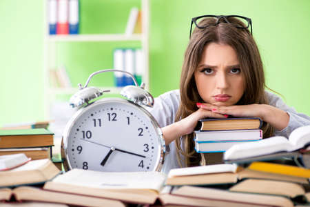Young female student preparing for exams with many books in time