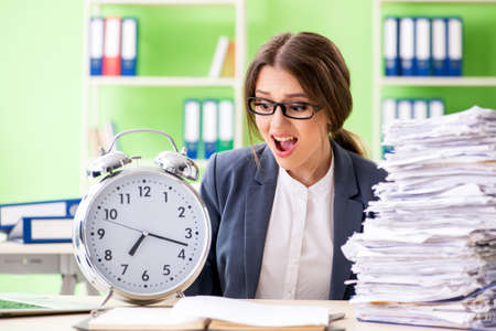 Young female employee very busy with ongoing paperwork in time management