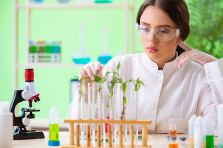 Beautiful female biotechnology scientist chemist working in lab