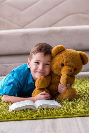 Petit garçon lisant des livres à la maison Banque d'images