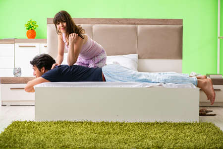 Woman doing massage to her husband in bedroom Stock Photo