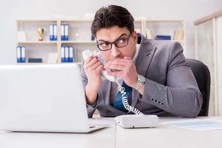 Homme d'affaires qui fuit des informations confidentielles par téléphone