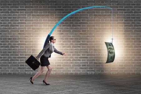 Businesswoman chasing money on fishing rod Stock Photo