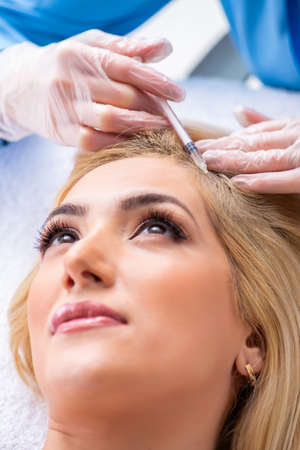 Plastic surgeon preparing for operation on woman hair Stock Photo