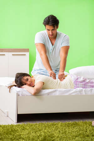 Man doing massage to his wife in bedroom Stock Photo