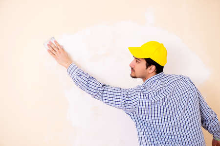 Young contractor sanding wall down with sandpaper
