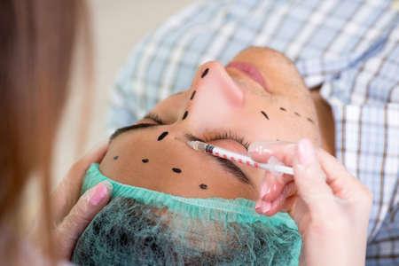 Plastic surgeon preparing for operation on man face