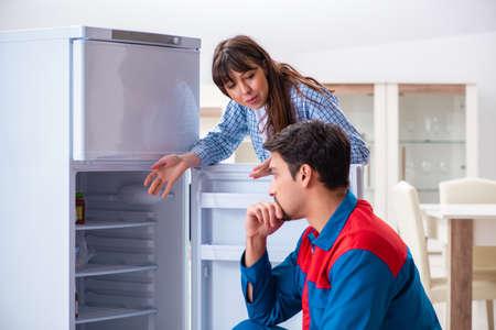 Man repairing fridge with customer Stock Photo