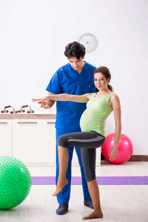 Pregnant woman doing physical exercies with instructor 写真素材 - 110194652