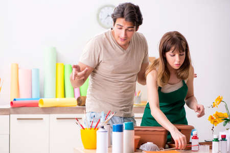 Couple decorating pots in workshop during class Stock Photo