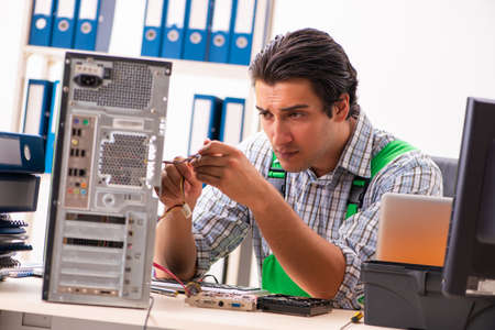 Young engineer repairing broken computer at the office
