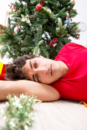 Young man drunk at home after christmas party Stock Photo