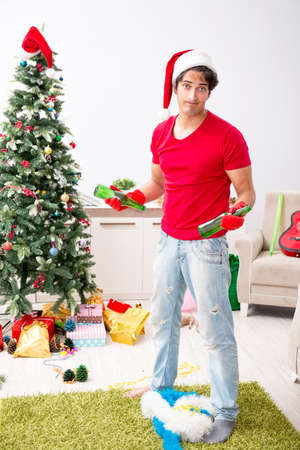 Man cleaning his apartment after christmas party Stock Photo
