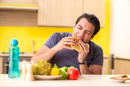 Man having hard choice between healthy and unhealthy food