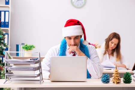 Man and woman working at the office on Cristmass eve