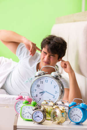 Young man having trouble waking up in early morning Stock Photo