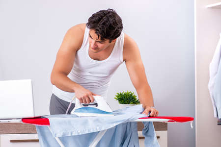 Young man freelancer ironing in the bedroom Archivio Fotografico