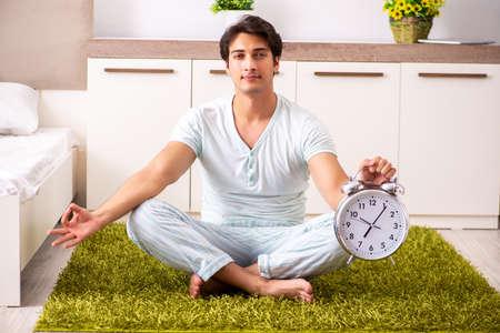 Junger Mann, der Yoga im Schlafzimmer im Zeitmanagementkonzept tut Standard-Bild