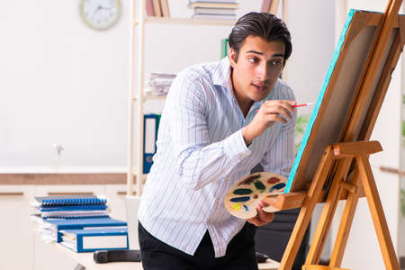 Young handsome employee enjoying painting at the office