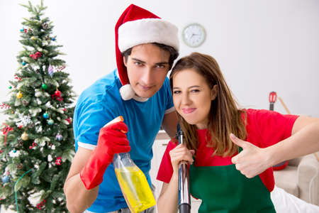 Young family cleaning apartment after christmas party