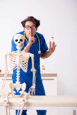 Funny doctor with skeleton in hospital Stock Photo