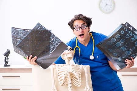 Funny doctor with skeleton in hospital Stockfoto