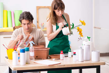 Couple decorating pots in workshop during class Foto de archivo
