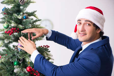 Young employee celebrating christmas at workplace