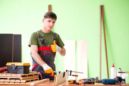 Young man carpenter working in workshop Foto de archivo