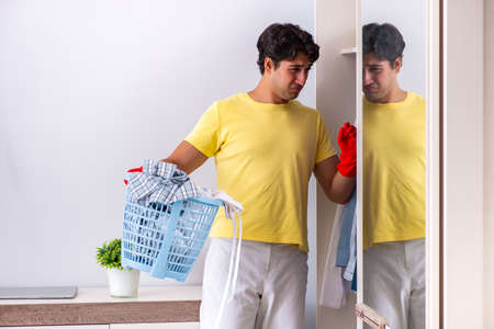 Young handsome man cleaning in the bedroom Фото со стока - 111389409