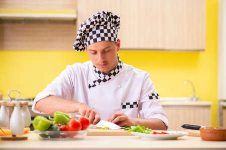 Young professional cook preparing salad at kitchen 版權商用圖片