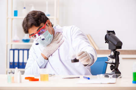 Young handsome chemist working in the lab Stock Photo