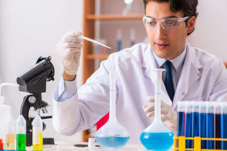Young handsome biochemist working in the lab Фото со стока