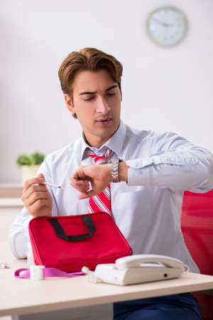 Man with first aid kit in the office
