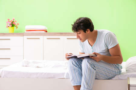 Young handsome student reading book in the bed Фото со стока