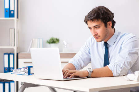 Young handsome businessman working in office