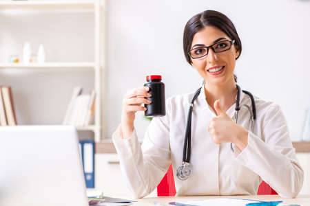 Woman doctor with bottle of medicines