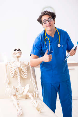 Funny doctor with skeleton in hospital Imagens