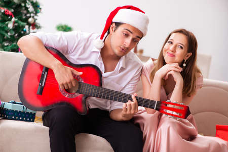 Young couple playing guitar at christmas